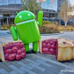 An Android robot with a cherry pie with a slice cut out of it.